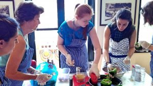 women are cooking around a table
